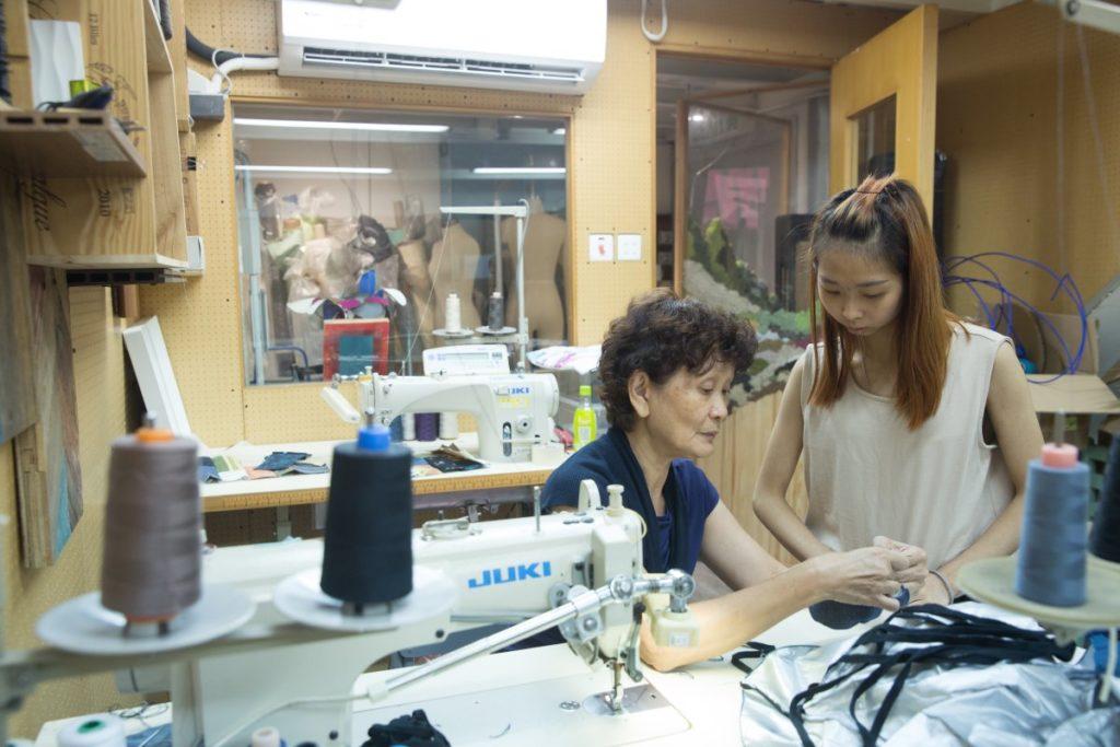 退休女工Janet(左)以往統領無數車衣工,如今指導年輕媽媽車縫拼布技巧。