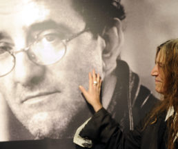 US singer Patti Smith poses in front of a giant poster of late Chilean writer Roberto Bolano in Madrid on November 26, 2010 during a ceremony at the Casa de America, announcing a week paying tribute to Bolano.   AFP PHOTO/ DOMINIQUE FAGET (Photo by DOMINIQUE FAGET / AFP)