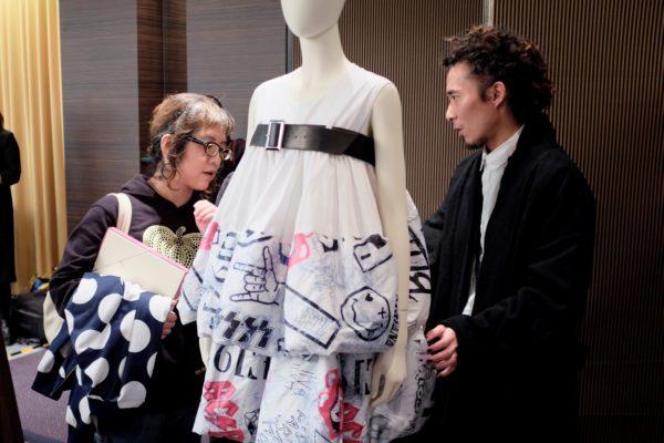 楊展(左)正向來訪者介紹他的最新系列FW18,系列融合了日本藝伎和搖滾的意念。