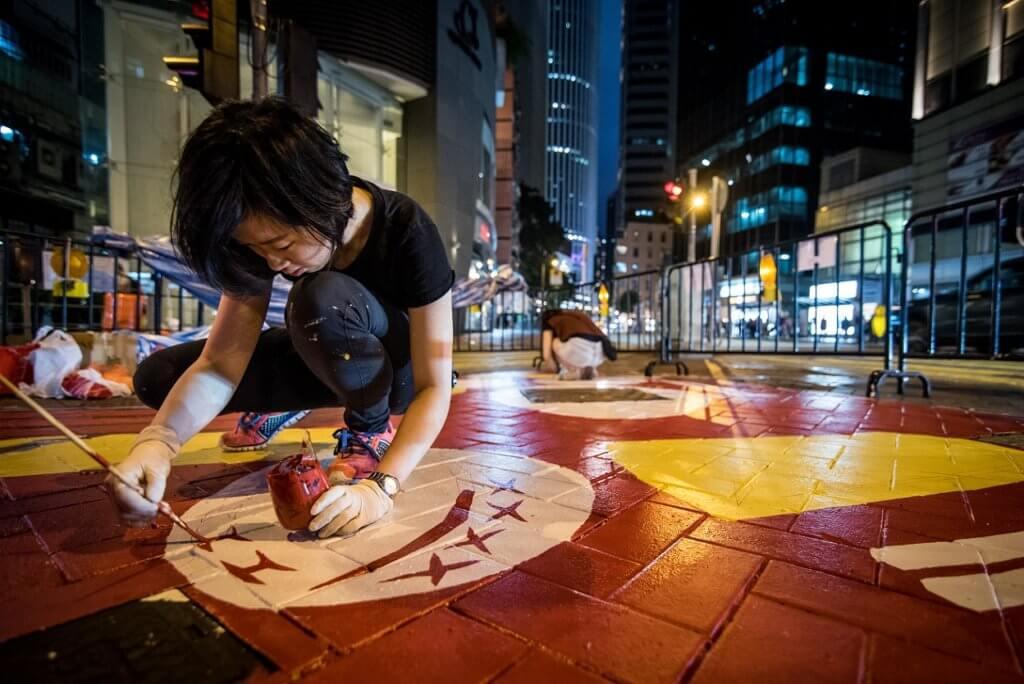 畫師晚間繪畫地面作品,以免影響白天路面情況。
