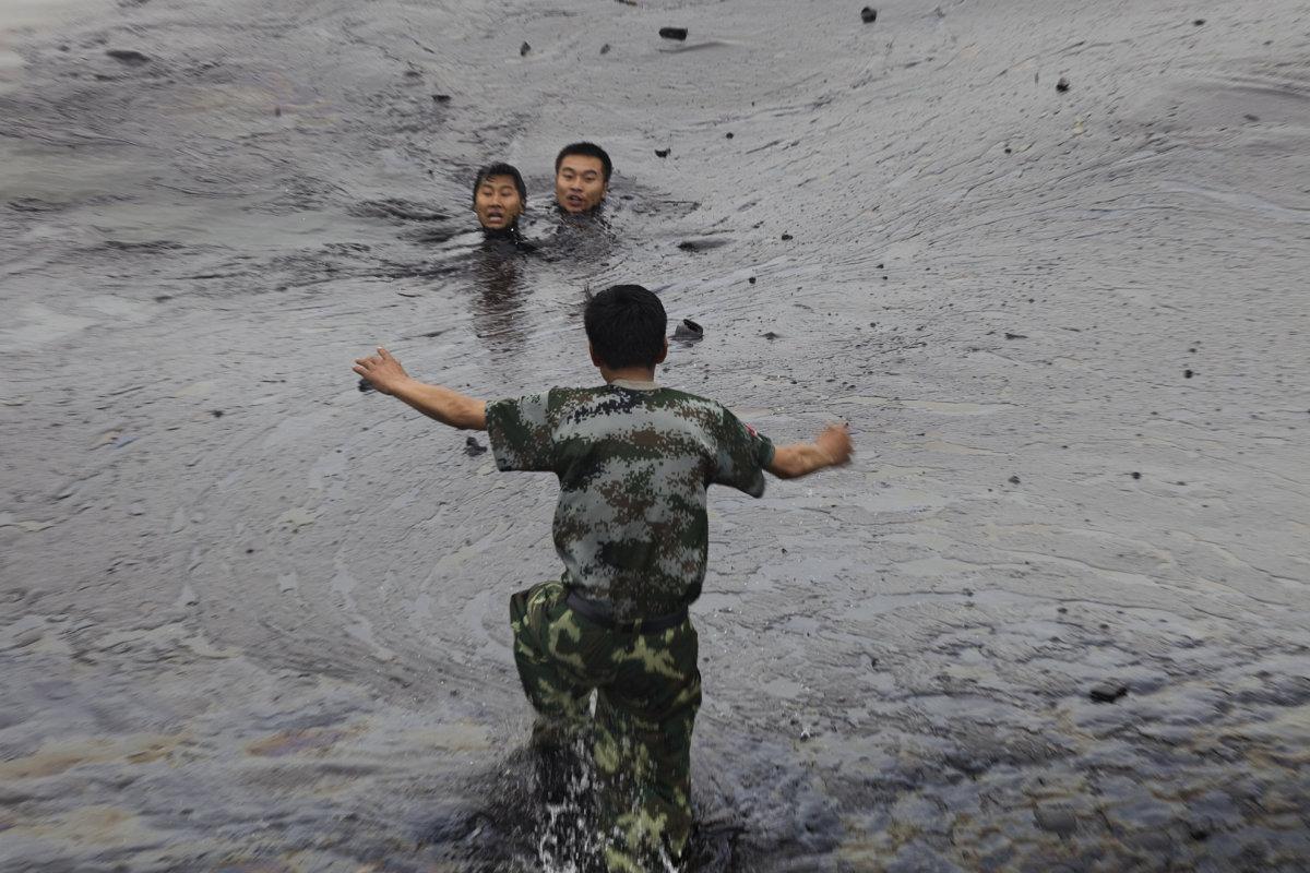 一名男子試圖營救兩名消防員張良和韓曉雄,兩人在厚厚的浮油中掙扎。張良(前)後來在石油中淹斃。