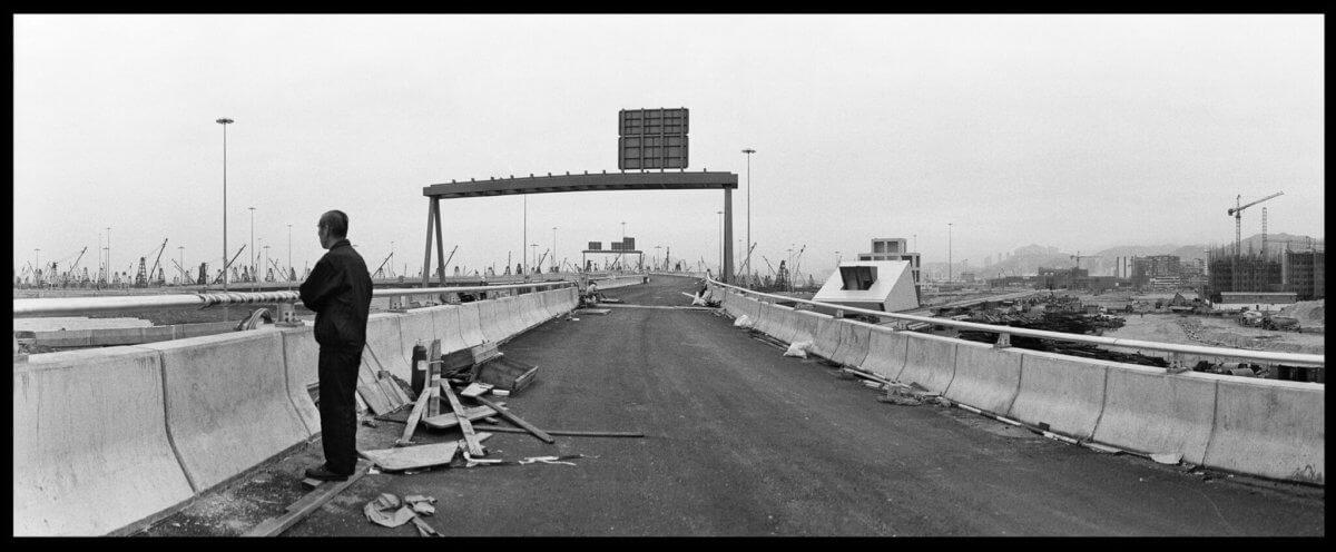 謝至德以抽離、靜觀內斂的角度,拍攝這片土地上的人事景物。他也運用不同攝影器材,圖為他在九十年代使用全景相機拍攝的西九高速公路,位置是油麻地,附近正在興建富榮花園。
