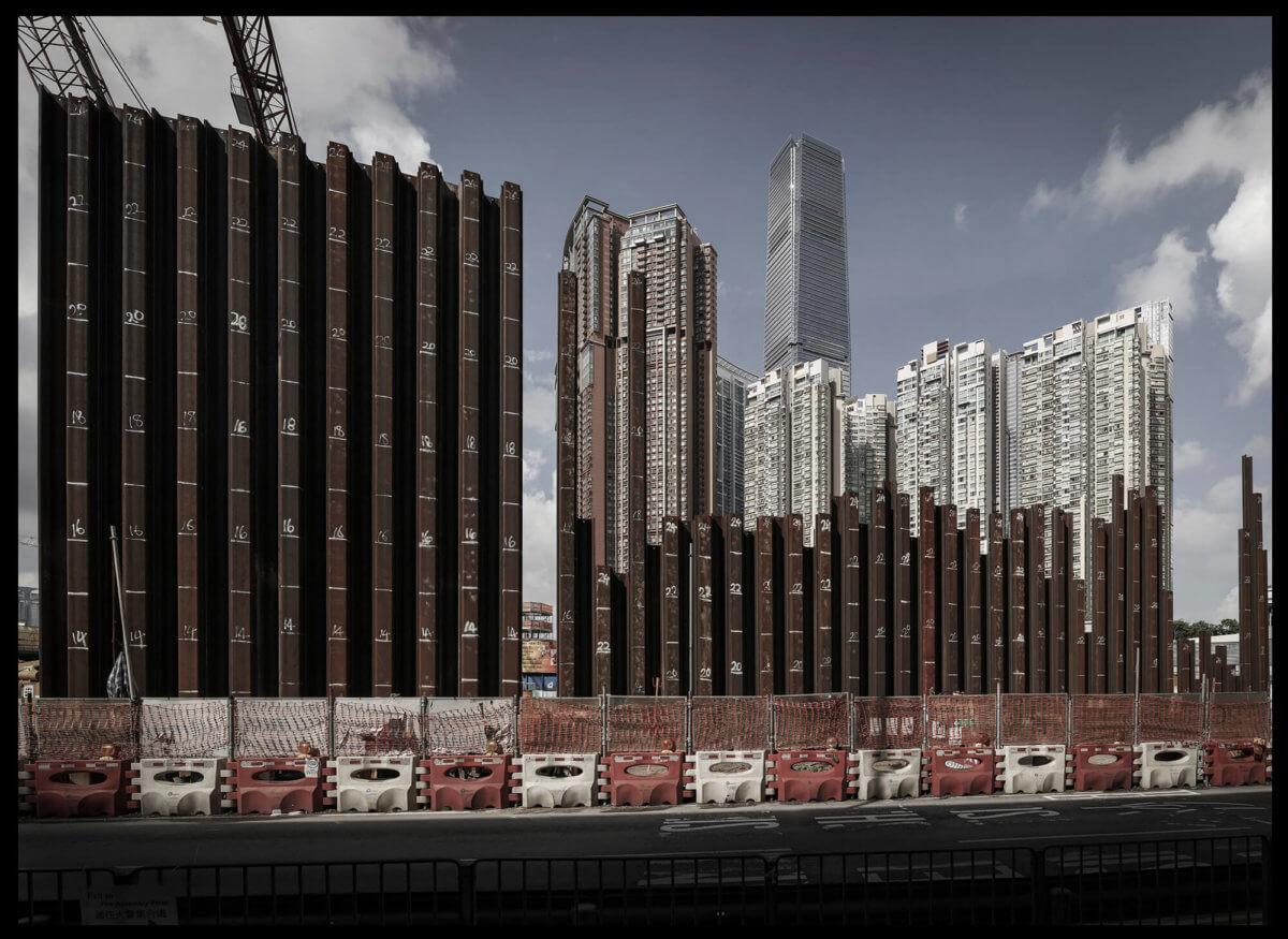 2012年,一列列樁柱象徵高鐵上蓋正進行樓盤工程。謝至德見證西九由填海變成目下的城市景觀,形容是一場「生死輪迴」。