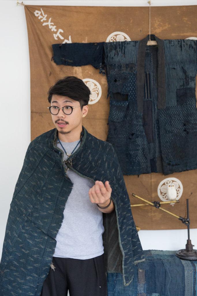 日本襤褸收藏家Brian,掛在牆上的襤褸是博物館級,外層布料已被風化;他身上披着的是「合羽」,江戶時代男性的輕便服,及後演變為「和洋折衷衣」。