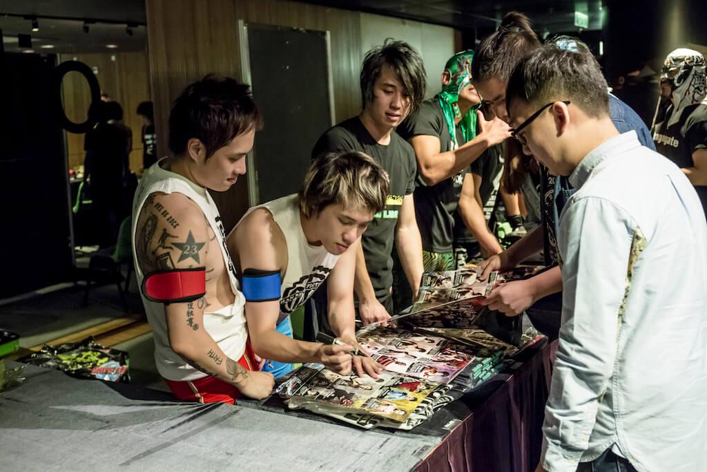 中場休息的時候,有觀眾買了印上The Man Bros的T恤,又請他們在場刊上簽名。