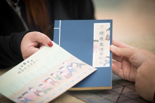 為了入學校宣傳而印製的筆記簿和年曆卡,由於包裝需時,技安找來阿盈幫手,與其他義工合力包裝二千五百份紀念品。