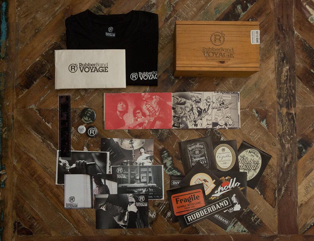 2009年,RubberBand首次在九展舉行演唱會,Kenji為他們製作了一百八十個木盒box set,內含書、T恤、菲林、貼紙、畫等東西,講述他們製作唱片的過程,亦回應第一隻碟《Apollo 18》說的情節——帶木盒上太空。 設計的紀念品,