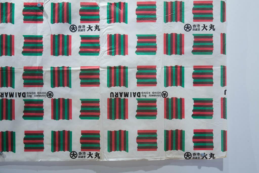 大丸百貨以三色印刷聖誕花紙,方格色塊其實只用了紅綠兩色,但套色重疊部分就多了暗灰綠這色,做法聰明。