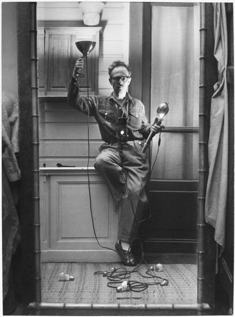 維利.羅尼木無表情地高舉閃光燈對鏡自拍,盡現其幽默感。《Self-portrait with flashbulbs》,維利.羅尼,1951年。