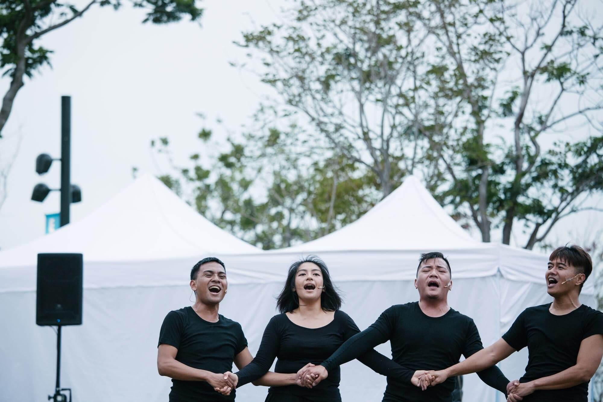 舞者穿着黑衫黑褲,在西九文化區的草地上,唱着歌,赤足跳舞。