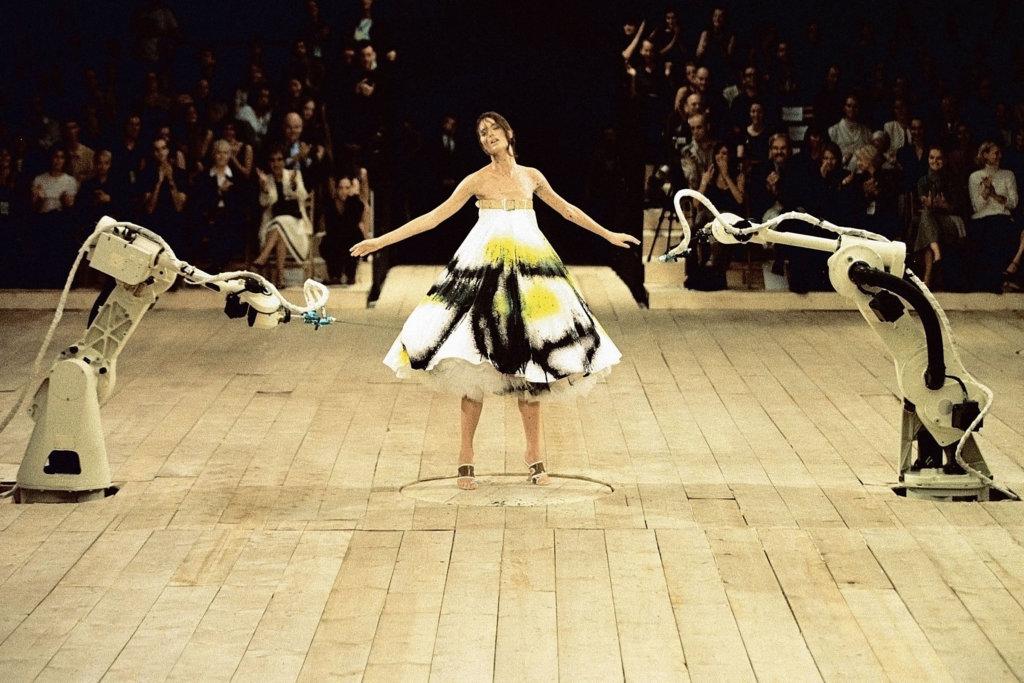 1999春夏系列《No.13》,模特兒Shalom Harlow身穿白裙站在中央的旋轉台,兩旁的噴墨機不斷噴出顏料,McQueen表示,第一次被自己的時裝騷感動。