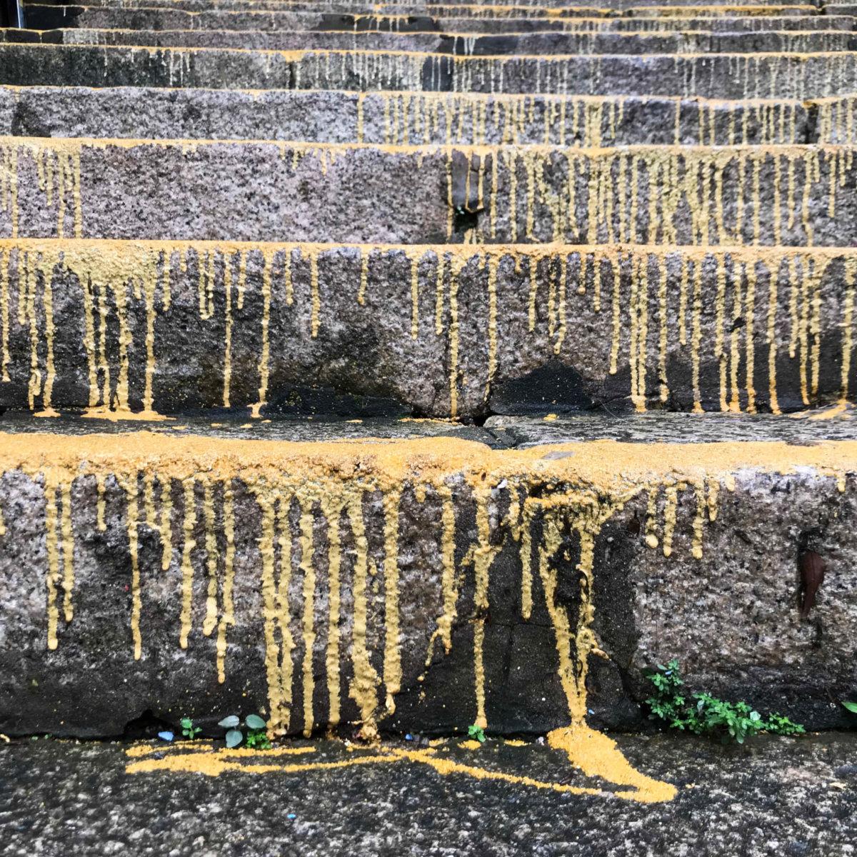 百年花崗石梯遭路政署淋上「防滑黃色鋼砂」,被批損害古物和造工粗劣,近期當局每日清理三級樓梯。