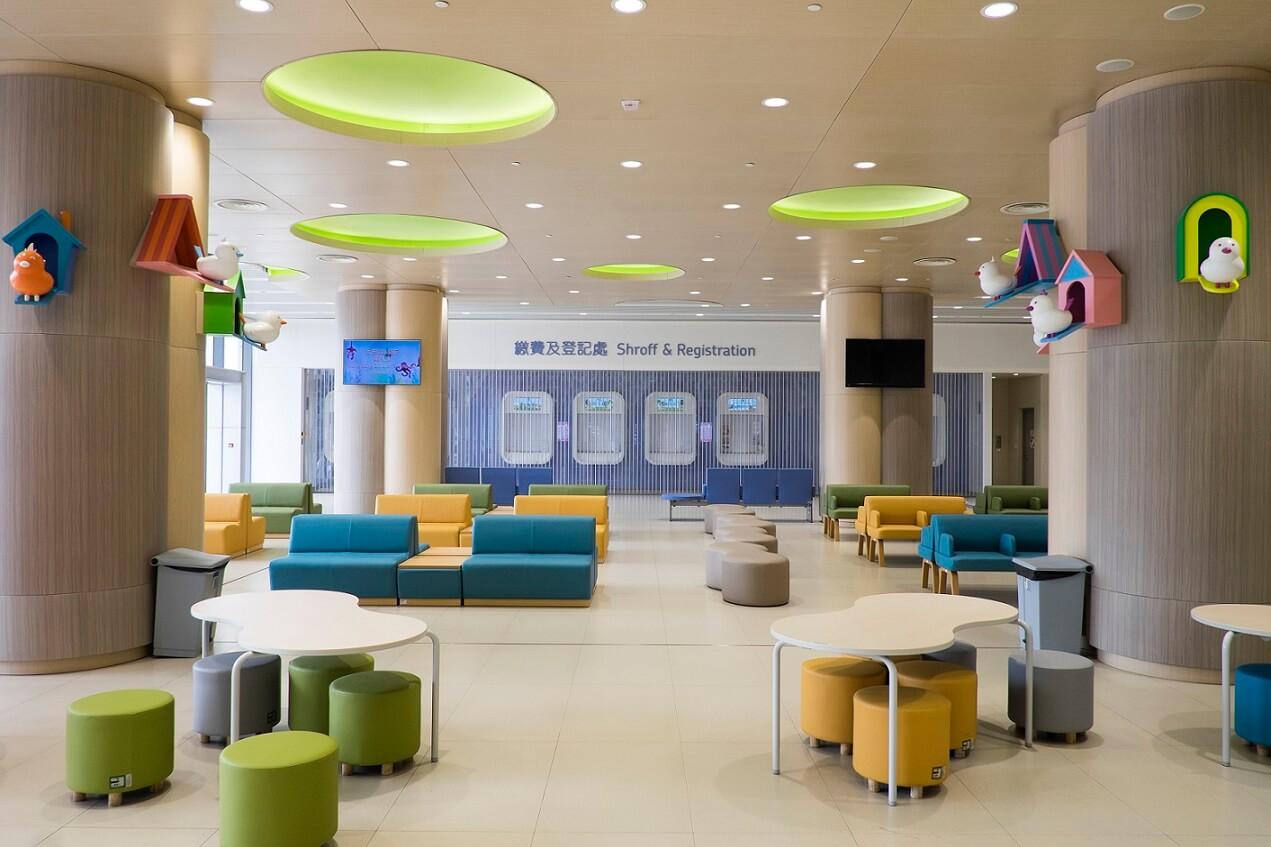 地下大堂繳費及登記處用色柔和。彩色梳化椅及矮凳,搭配可愛小鳥裝飾,一洗醫院冰冷感。