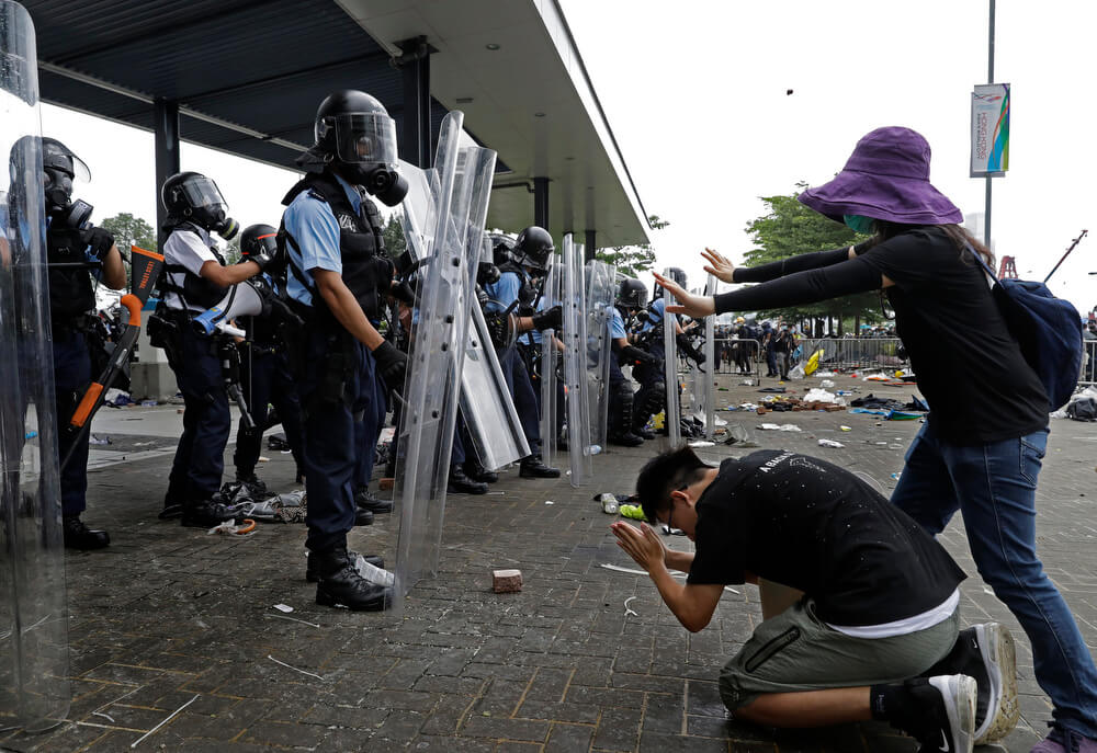 A protester bows to riot police after they fire tear gas towards protesters outside the Legislative Council in Hong Kong, Wednesday, June 12, 2019. Hong Kong police used tear gas and high-pressure water hoses against protesters who had massed outside government headquarters Wednesday in opposition to a proposed extradition bill that has become a lightning rod for concerns over greater Chinese control and erosion of civil liberties in the semiautonomous territory.(AP Photo/Vincent Yu)