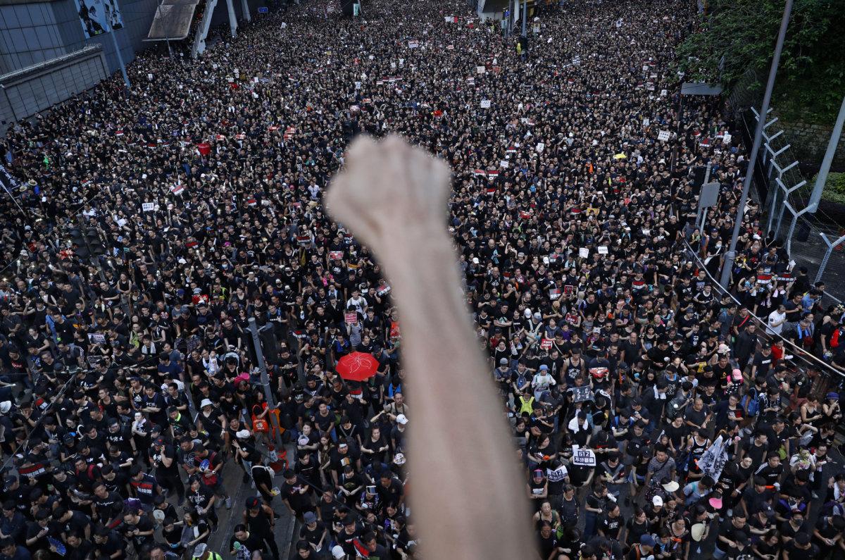 6月16日,「反送中」第四次遊行,引發二百萬人上街。 當日余偉建跑到金鐘道一條行車天橋,拍攝萬人空巷 的遊行情況。橋上,他遇見一名正舉起手、呼喊着口 號的示威者,「這隻手,代表抗爭」,於是他按下快門 記錄這一幕充滿象徵意義的歷史瞬間,並成為世界各 地的報章頭條。(AP Photo/Vincent Yu)