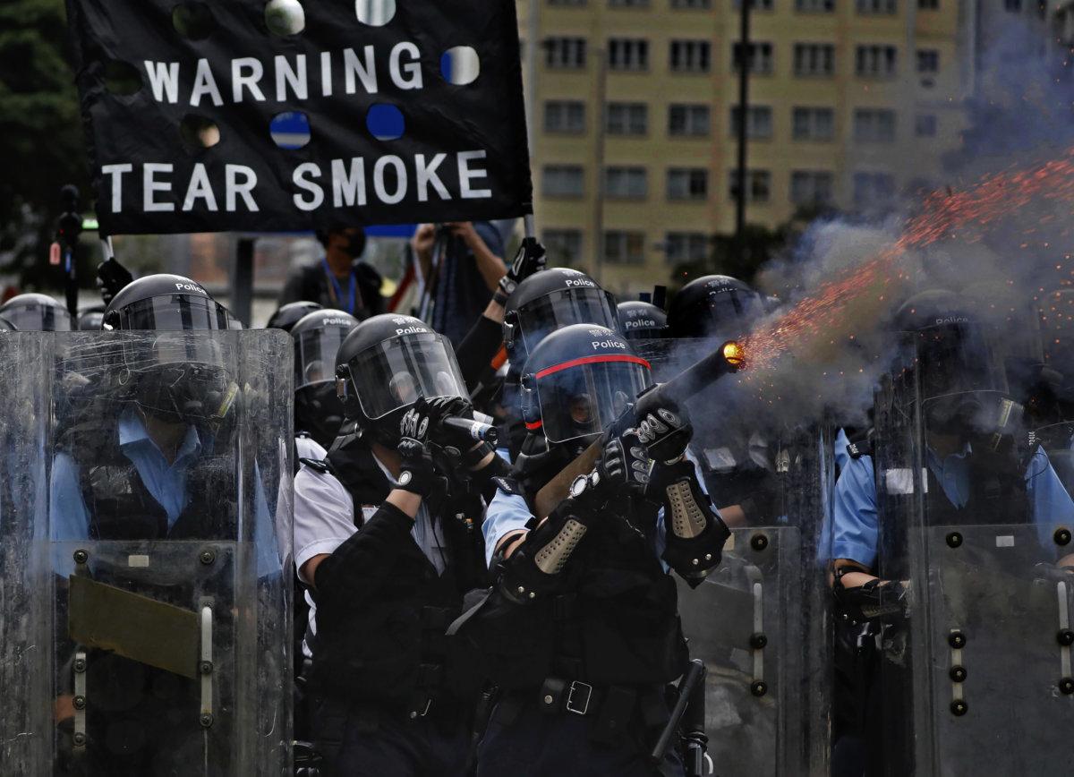 6月12日,警方於金鐘一帶施放催淚彈驅散示威者。余偉建在拍攝期間,多次被煙霧弄至眼部不適、喉嚨乾涸及呼吸困難,「有十數分鐘痛苦得失去行動能力,曾有警察遞上一清水給我洗眼,這次催淚彈的殺傷力,比反世貿和9.28雨傘運動更嚴重。」(AP Photo/Vincent Yu)