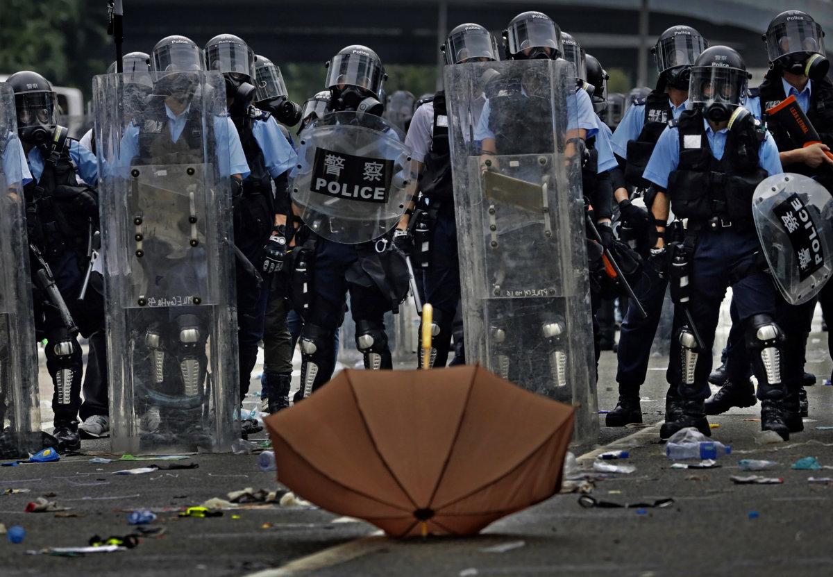 6月12日,警方施放一輪催淚彈後,於夏愨道與示威者對峙。「防暴警察面前,有一把孤獨的雨傘,當時示威者再沒上前衝擊警方陣線,但未幾,警方再次施放催淚彈。」(AP Photo/Vincent Yu)