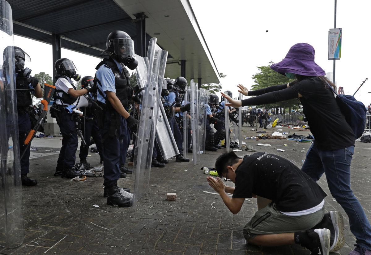 6月12日,立法會門外,示威者向警方跪求停止使用暴力。當時情況,物件散亂一地,警察的腳邊有一塊磚頭。(AP Photo/Vincent Yu)