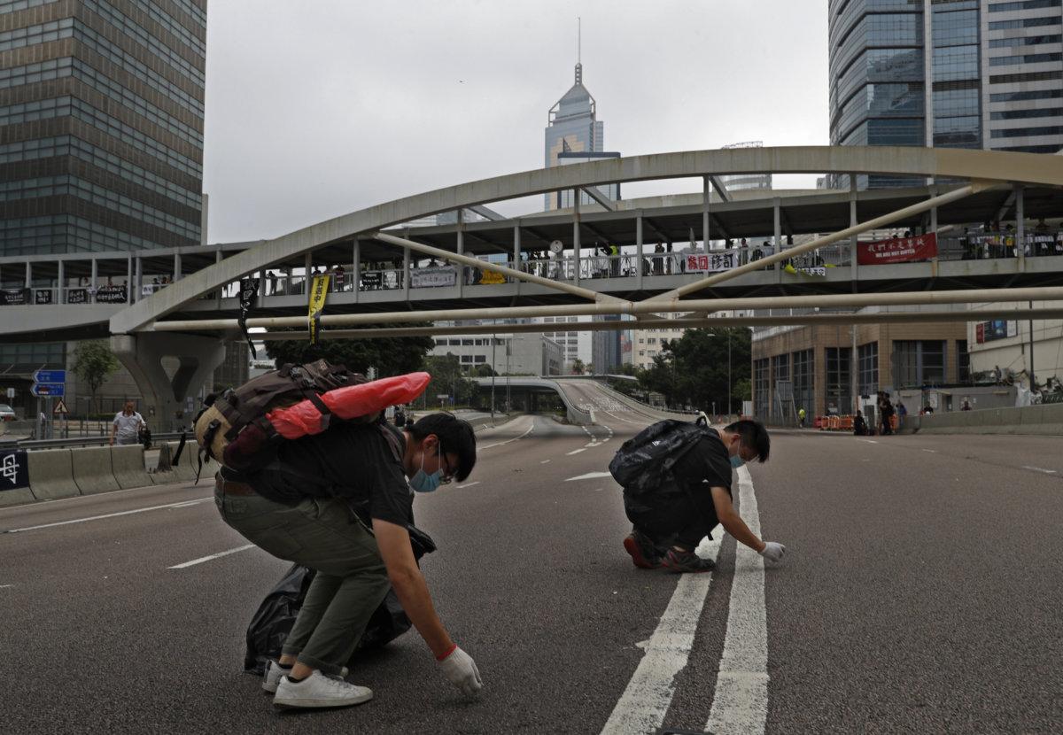 6月17日,早上8時左右,警方計劃重開夏愨道,呼籲示威者和平離開,並強調並非清場。「那一幕很深刻,第一次看見示威者勸告同行者退場,並且逕自把現場的物件清理乾淨才離開。」(AP Photo/Vincent Yu)