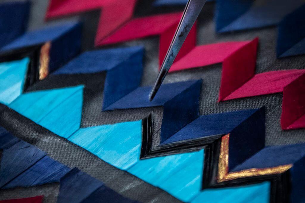 Lemarié為了製作綴滿幾何圖案的羽毛長裙,先要將每塊羽毛染成紅、深藍、綠松石和黑色,再在羽毛上手繪金色筆觸。處理好羽毛之後,再人手切割成幾何圖形,一行一行地嵌到黑色紗裙之上。