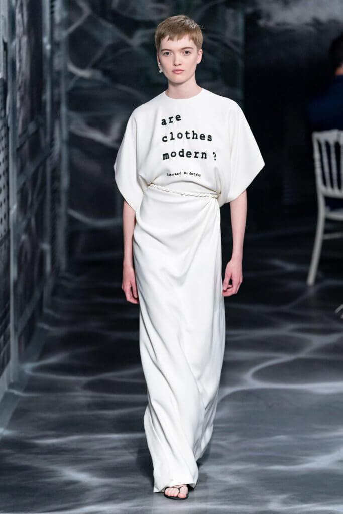 """出場的白色連身裙靈感來自希臘的寬身長袍péplos,胸前則用無數顆黑珠繡着""""are clothes modern?""""。"""