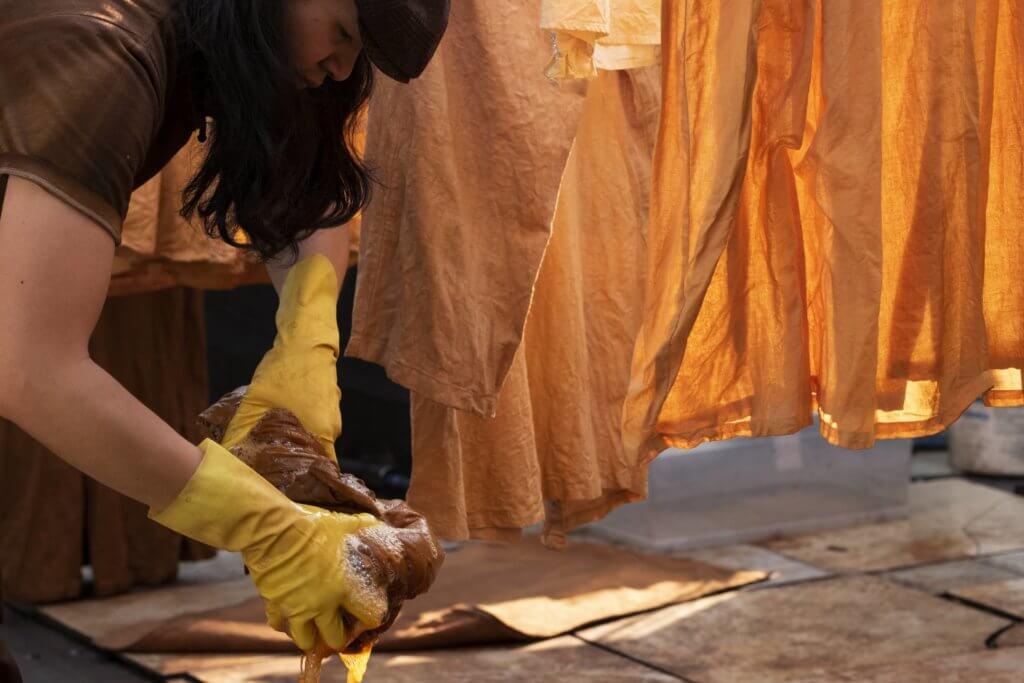 莨染首先將薯莨切碎,再榨汁,提取汁液﹔混合水把衣服一同浸泡,並放在太陽下晾曬至少兩星期。完成後,再將布料塗上蠟,營造破舊的感覺。
