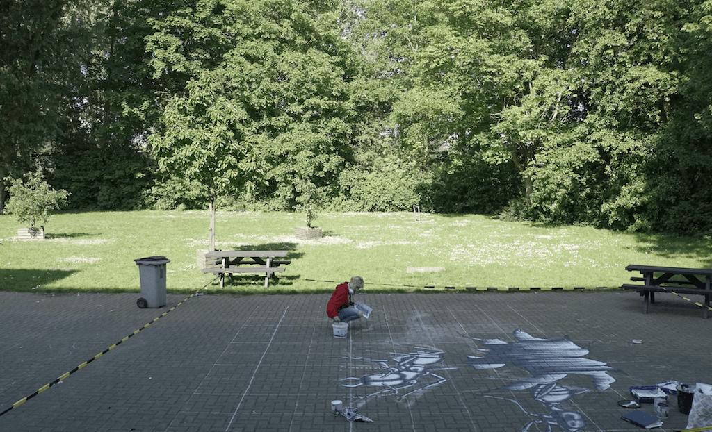一個中學生在 學校空地畫畫,偌大的磚地就是最自由的畫紙。