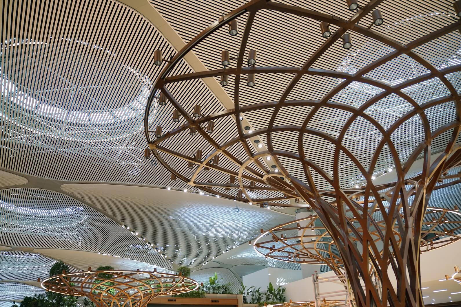 天花的弧形三角結構,呈彎月圖騰,與模擬樹木裝飾的線條匹配。