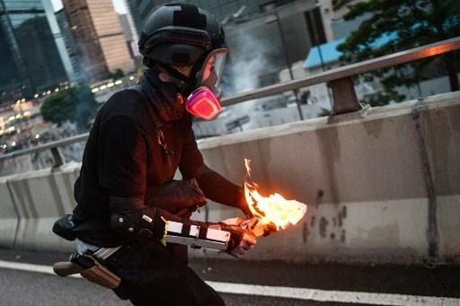 投擲汽油彈的示威者,被拍到腰間有槍狀物體,示威者身份成疑。(攝影:Anthony WALLACE / 法新社)
