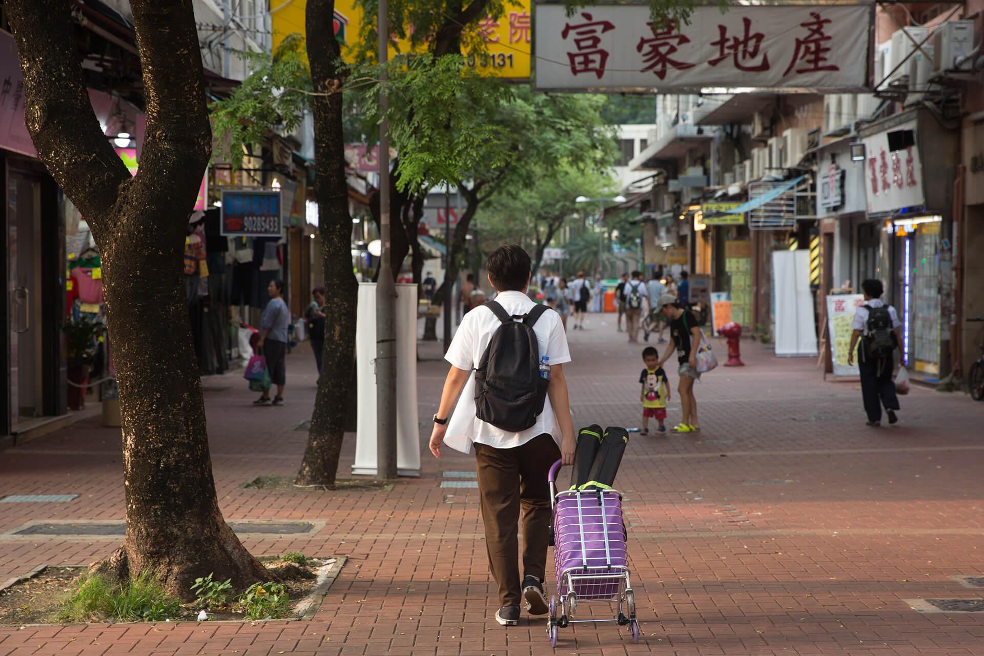 張可森以一身文青打扮,拖着一個略嫌有點違和的紫色手推車落區設街站。