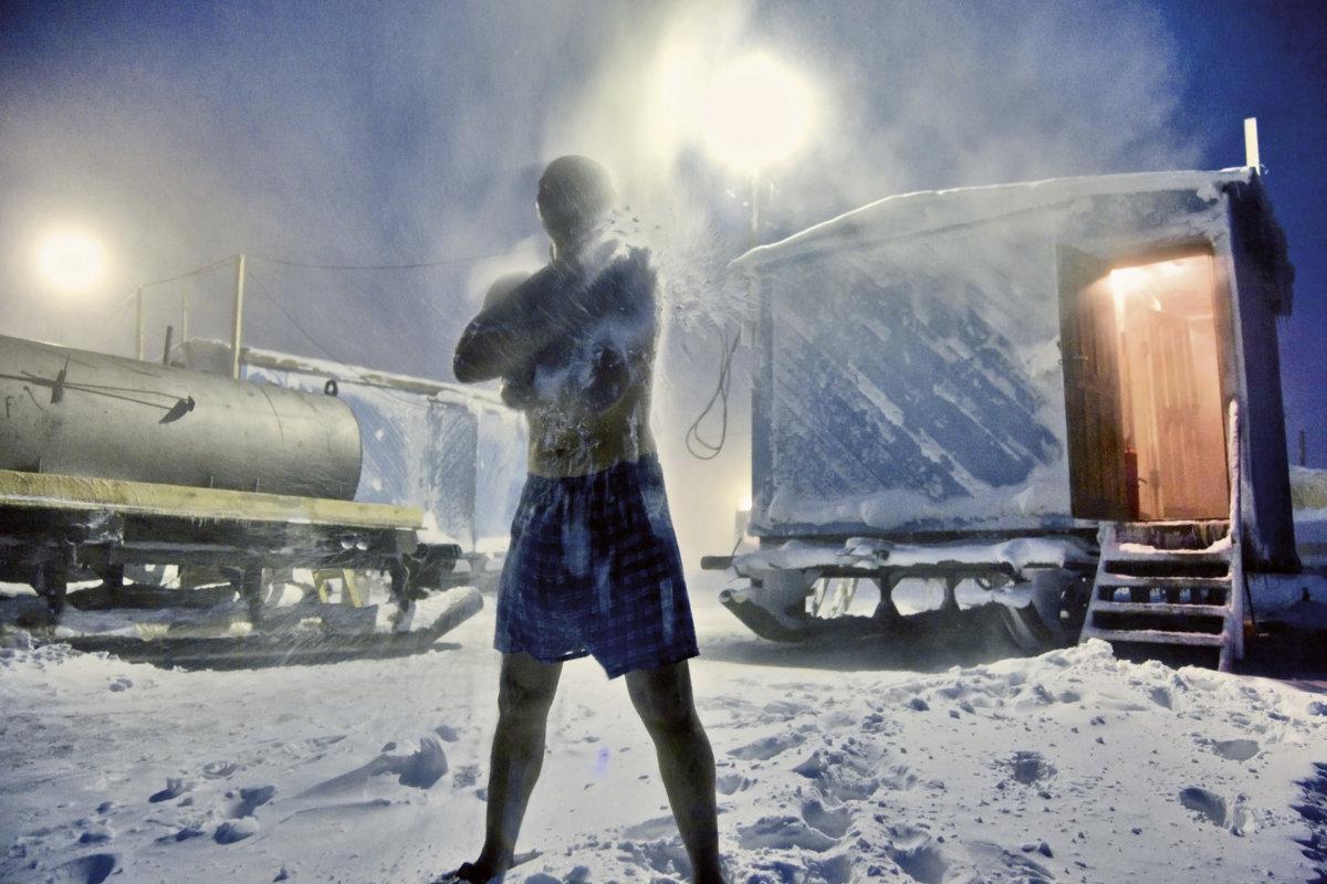 一名石油勘探人員在蒸桑拿的過程中用雪擦身,水是由圖左側的柴油罐車加熱的,熱力就來自地下的石油。他們整個冬天都在寒冷偏僻的荒野中工作。