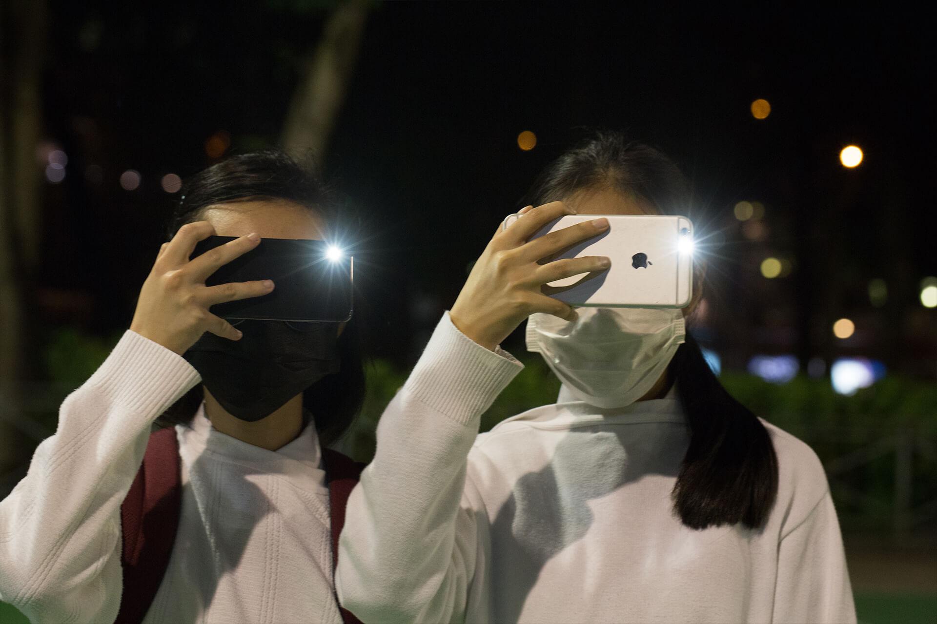 Hoaa(左)與她的朋友穿著校服參與網民發起的「球迷大和解」人鏈大合唱活動。以往她很討厭大合唱,現在卻從大家的歌聲得到力量。