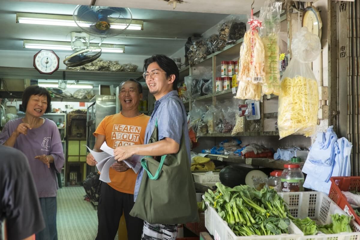 「坪洲島聚」發起人徐逸朗( 右一)在坪洲商店街宣傳中秋活動時,店舖東主友善歡迎。
