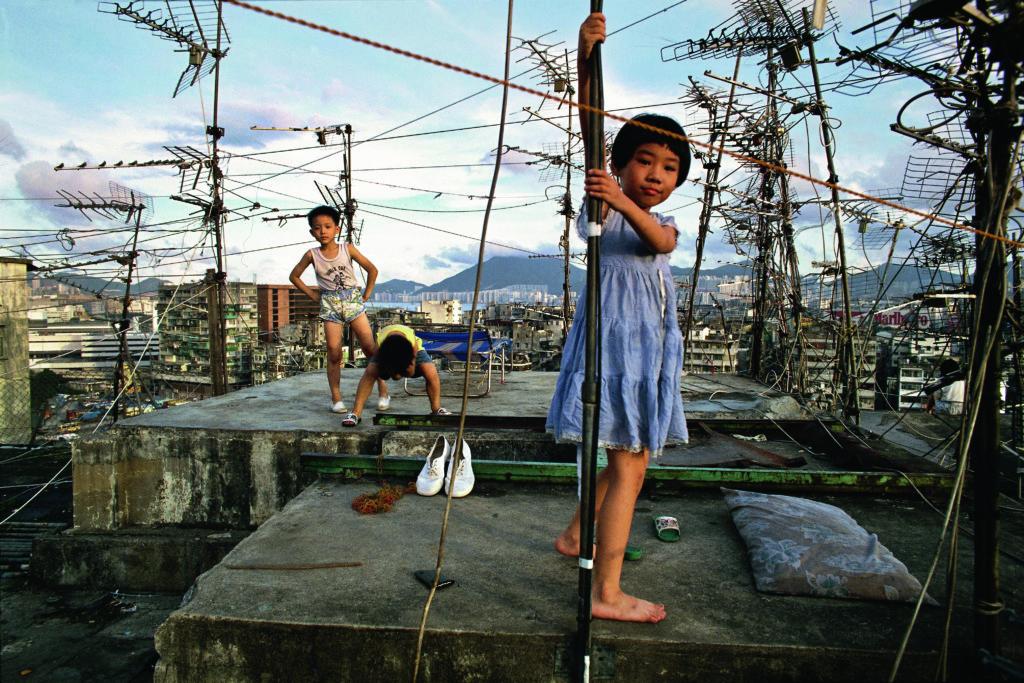 Greg Girard拍攝城寨人的生活面貌,小朋友們在凌亂的天線架下玩樂。