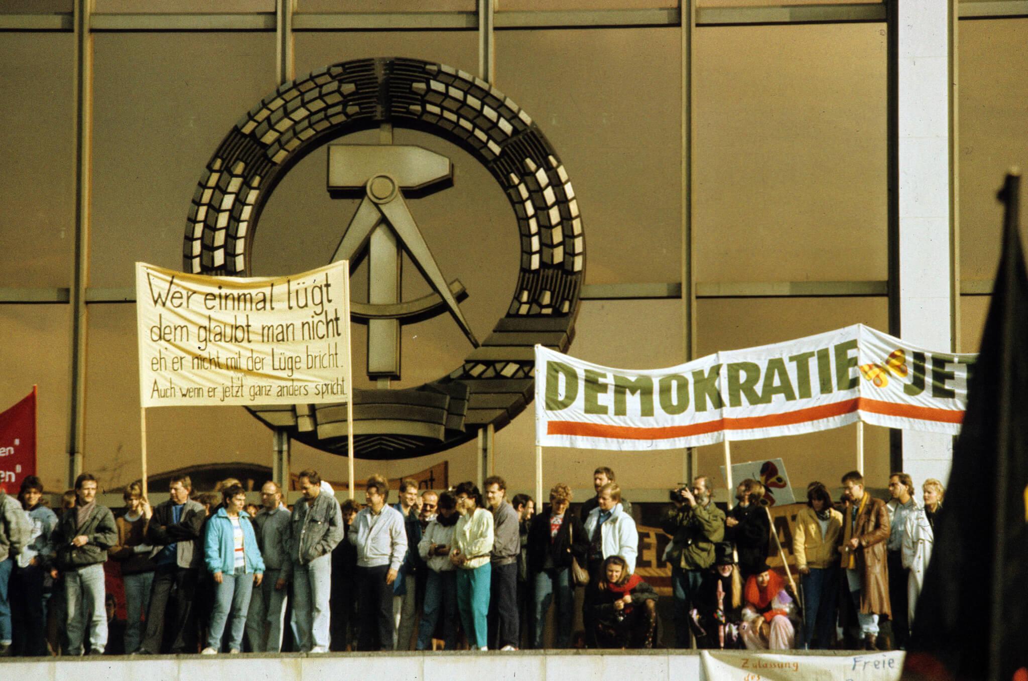 1989年11月4日,成千上萬的人聚集在柏林亞歷山大廣場周圍的街道上,為德意志民主共和國變革而遊行,在共和國宮(德語:Palast der Republik)橫幅上寫着:「一次說謊,永遠說謊……」和「民主」。(圖片:法新社)