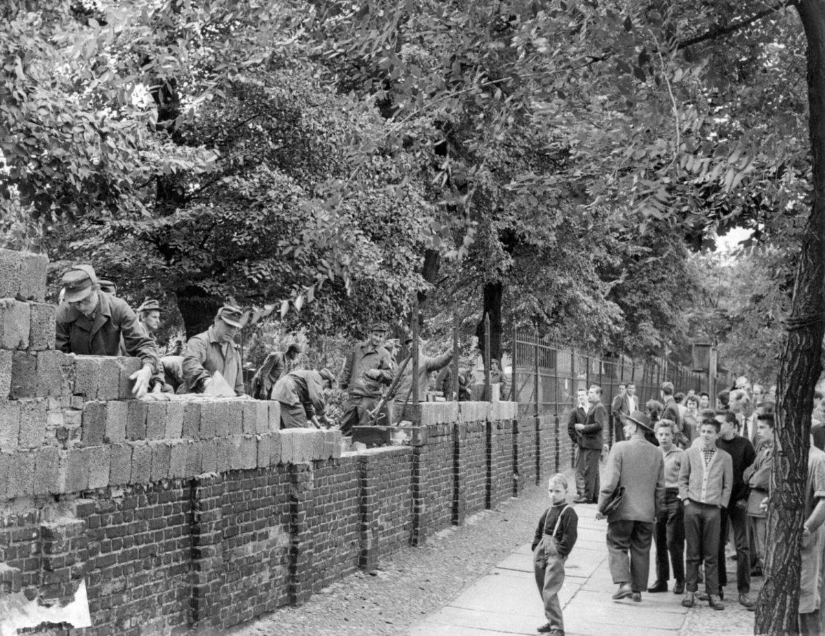 1961年8月15日,東德工人建立一段柏林牆,人們從西柏林圍觀。(圖片:法新社)