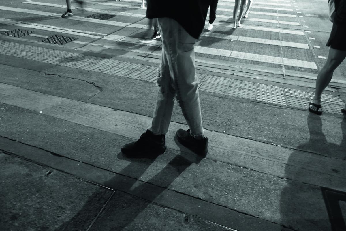 年輕的旁觀者在太子港鐵站外的8.31「紀念壇」不安地交叉雙腿站立,攝於2019年9月25日。