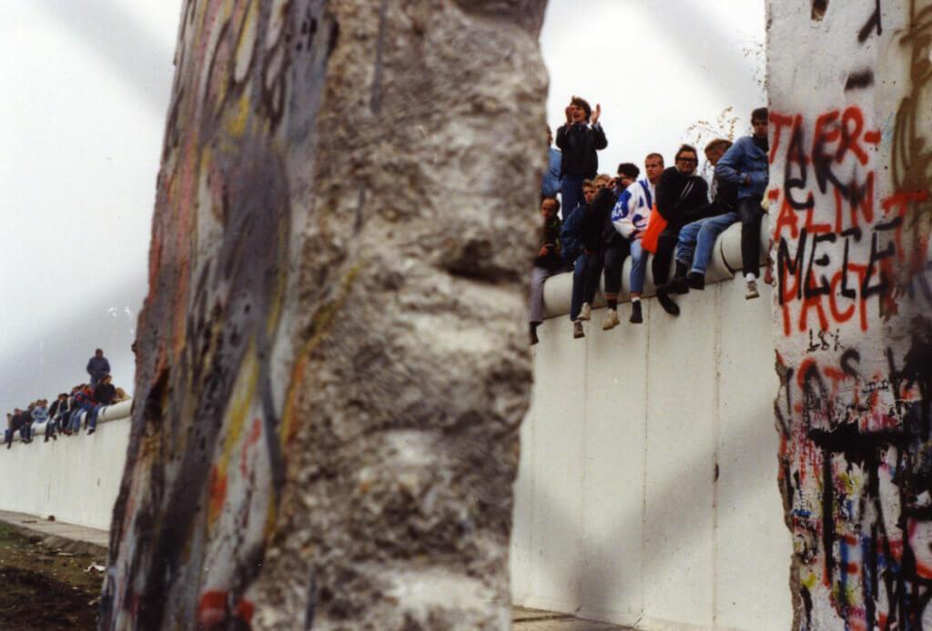 1989年11月12日,在剛開放的邊境口岸波茨坦廣場上,許多人坐在牆上歡慶。 ©Berlin Wall Foundation, Photo: Nicole Monterán
