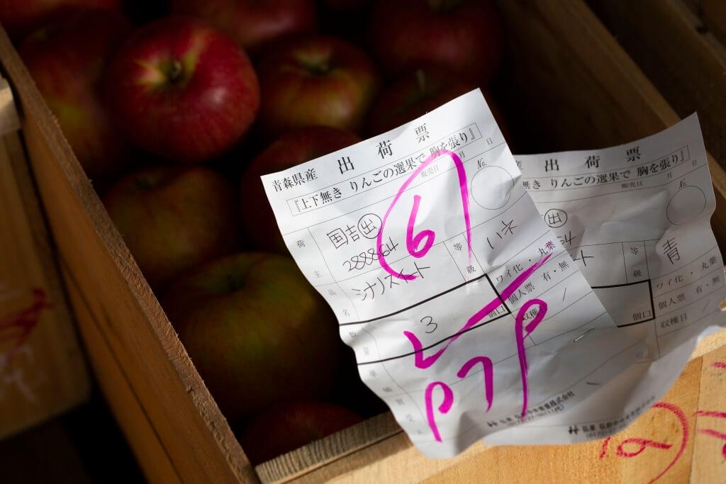 投得的蘋果會附上單據,上面分別列出投得者、蘋 果的果種、箱內的容量、蘋果的級別及價錢,然後 準備出貨。
