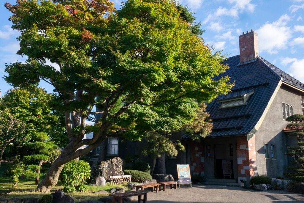 紅色磚瓦屋頂,褐色的煙囪,深灰色的房子,格紋窗花,外形有別於附近的和式建築。