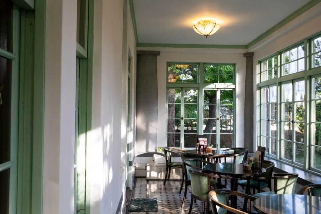 木地板轉變成八角形和四方形的地磚,擺放了木圓 桌以及有手柄的絲絨木椅,彷彿坐在英式茶室內。
