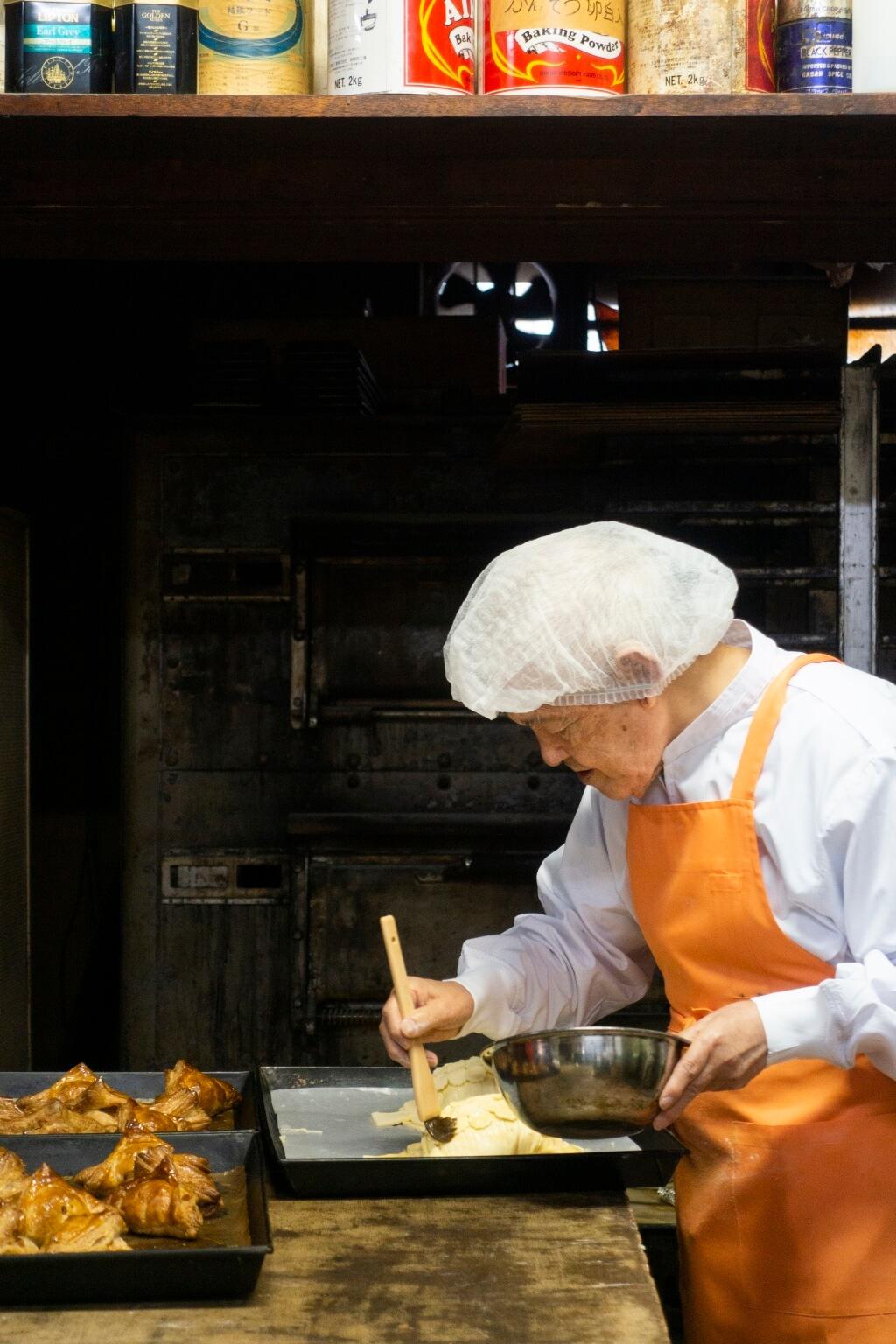 82歲的葛西清逸,在小學時已有做餅廚的 志願。於是高中時開始半工讀,到橫濱的西餅 店學藝。現時他仍會天天到餅店親手製作蘋果批。
