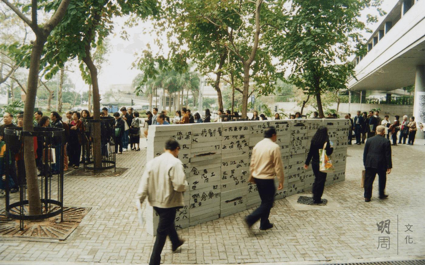 《驅動器》(1996),林在藝術中心外建起一道高牆,磚上寫上不同的政黨名字,這磚牆剛好遇上移民潮排隊申請BNO的人龍。