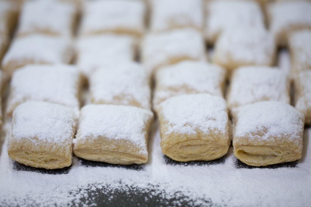 在焗好的枕頭酥面上灑上大量糖霜,再翻局一次,至糖霜微焦,甜中帶微燶味,更香口。