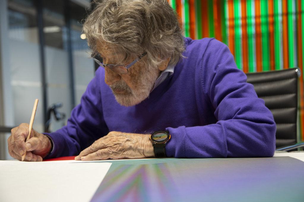 carlos-cruz-diez-signing-an-artwork-in-his-workshop-paris-france-2018-photo-atelier-cruz-diez-paris-lisa-preud-homme