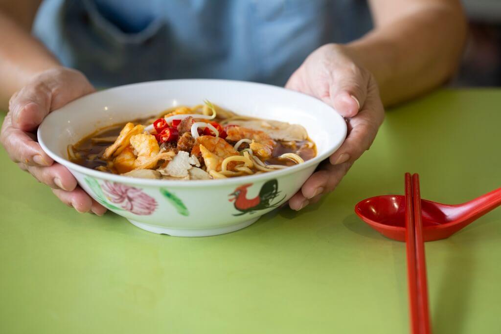 蝦麵 這碗蝦麵有着三代堅持不懈的努力: 由李瑞芳祖父李承竹於1930年代以 擔挑賣麵開始至今。另有乾的拌麵版 本,吃來更香辣。(SGD $4)