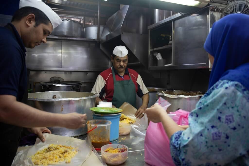 店子廚房現時由父親Hamid (中)及兒子Hannan(左)主 理,Hannan的阿姨(右)則負 責接柯打和收錢。