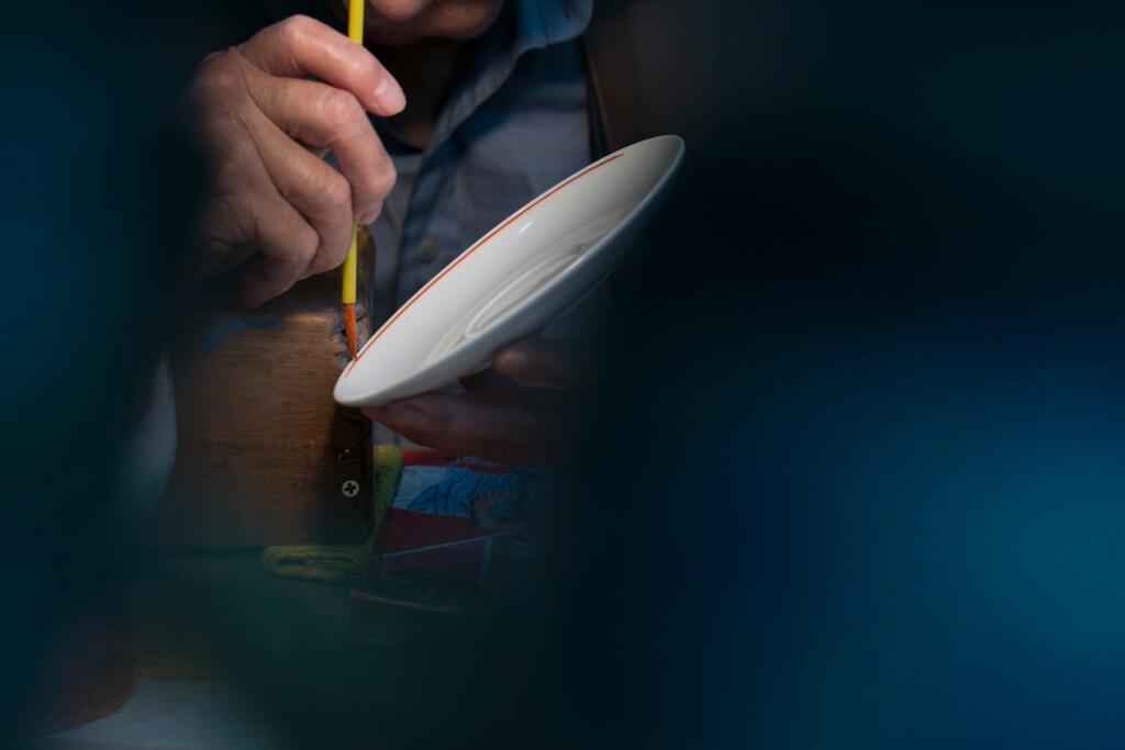 粵東磁廠依然保留人手上釉的 工藝,現存多為做了超過四十 年的老畫師。由過去複雜的廣 彩和粉彩到近年貼花較為普及, 一來工夫較少,二來成本較低, 一日左右便能起貨,比傳統廣 彩足足節省一半時間。