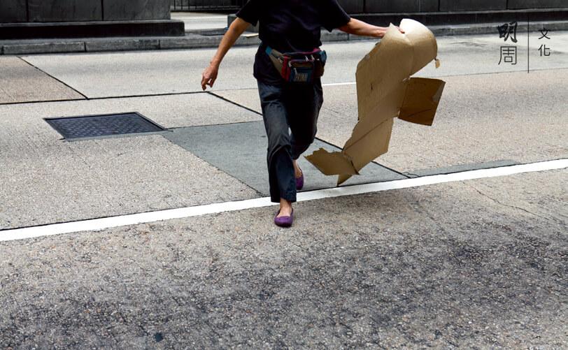 馬路對面有一塊紙皮,她趁沒車衝了過去撿。