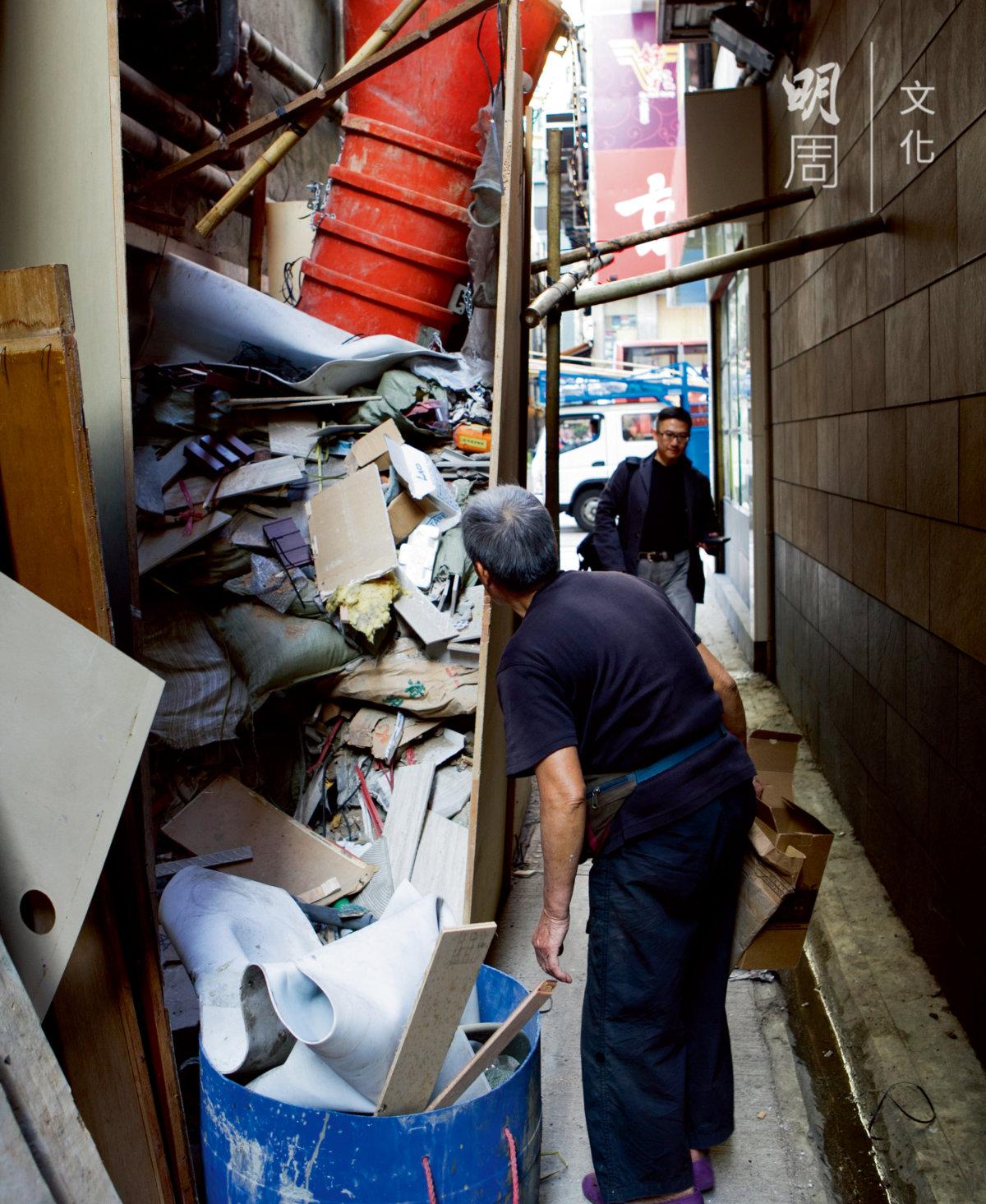 她在一堆建築廢物中拖出一小塊紙板,廢料差點傾瀉而下。